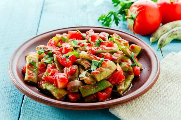 тушеная с томатами фасоль в тарелке на столе