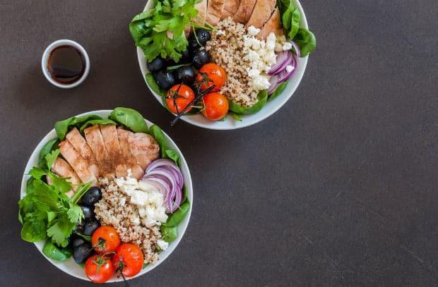 киноа с курицей и овощами на тарелках на столе