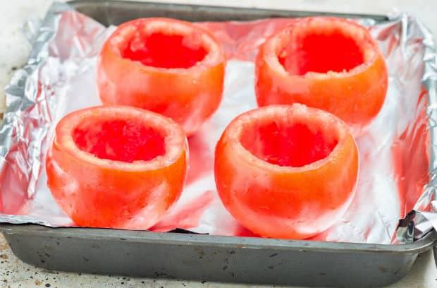 четыре обрезанных помидора на противне
