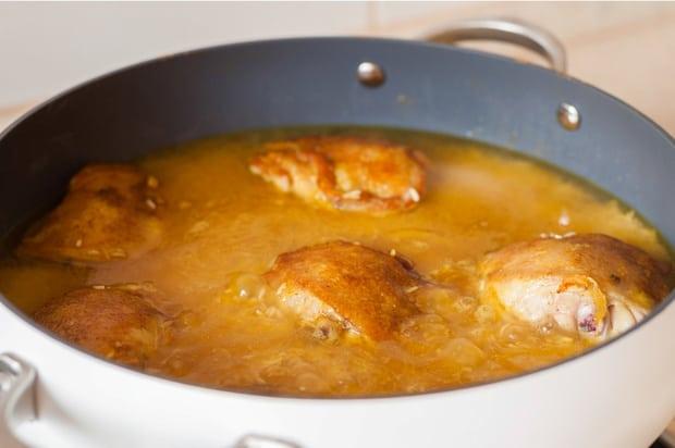 жареные куриные бедрышки, залитые водой, в сковороде