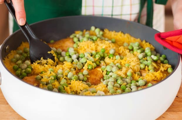 зеленый горошек поверх тушеного риса с куриными бедрышками с лопаткой в сковороде