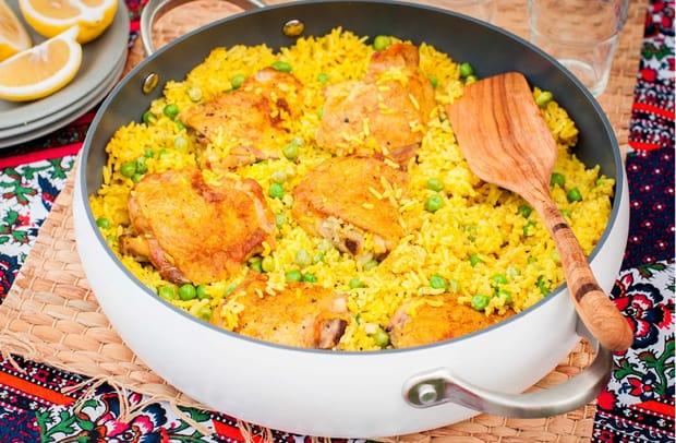 тушеный рис с куриными бедрышками и зеленым горошком в сковороде с лопаткой на столе, застеленном скатертью, рядом дольки лимона