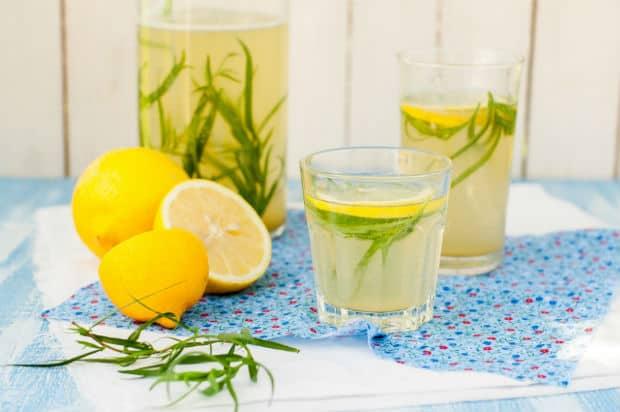 два стакана и графин с лимонадом и веточками эстрагона, рядом половинки лимона и зелень на столе, застеленном скатертью