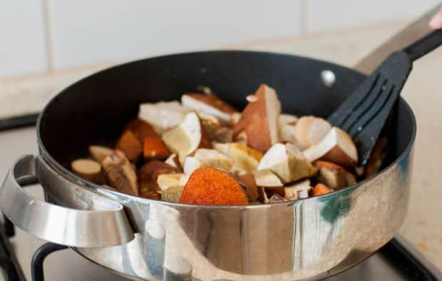 нарезанные лесные грибы в сковороде на плите