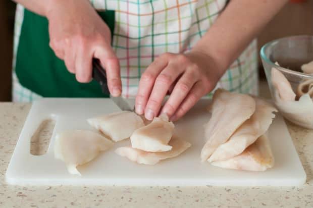 филе рыбы нарезается на разделочной доске