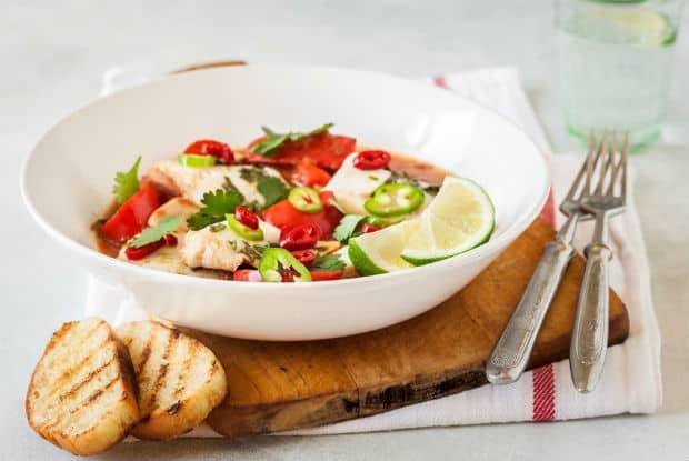 рыба, тушенная с овощами, в белой тарелке