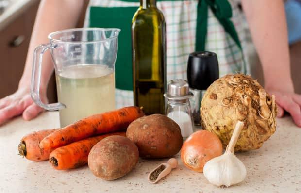 чеснок, луковица, картошка, морковь, баночки со специями, бутылка оливкового масла, бульон в графине, корень сельдерея