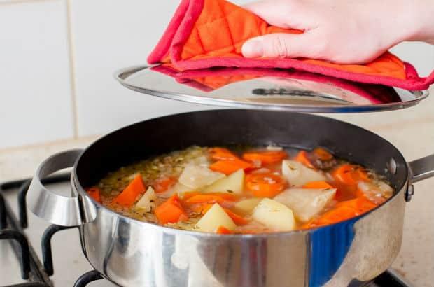 тушеные морковь, картофель и корень сельдерея с бульоном в сотейнике
