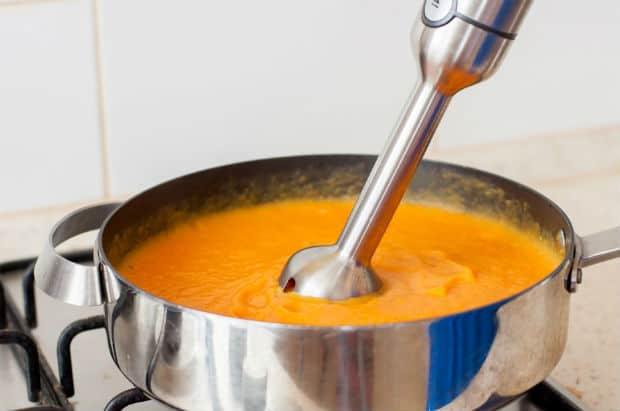 готовый суп-пюре из моркови с погружным блендером в сотейнике на плите