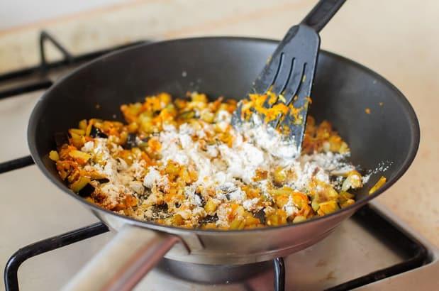 лук, морковь, кабачки и лук в сковороде с мукой