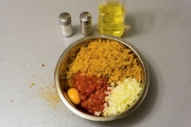 фарш с сухарями, луком и яйцом в миске