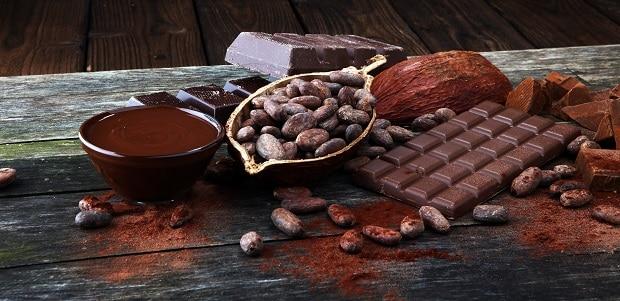 бобы горького шоколада, рядом шоколадная плитка и растопленный шоколад