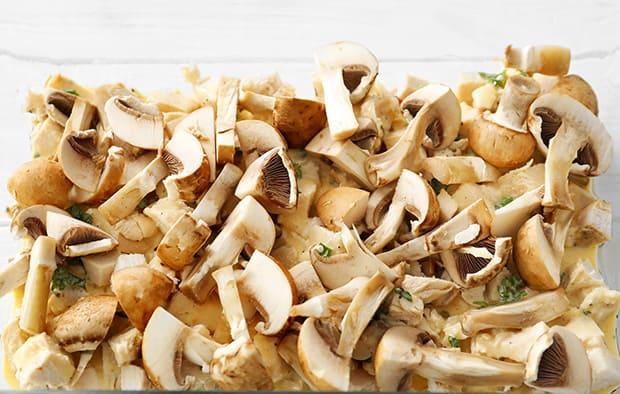 нарезанные грибы поверх кусочков филе индейки в форме для запекания