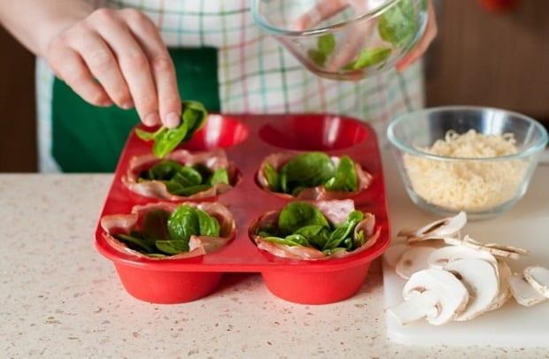 листья шпината выкладываются в красные силиконовые формочки, рядом тертый сыр в пиале и нарезанные шампиньоны