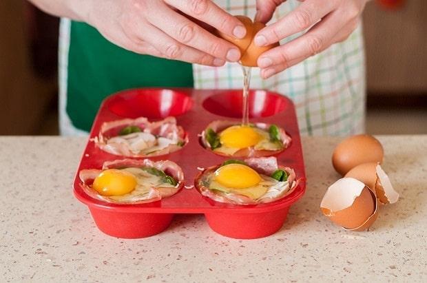 куриные яйца разбиваются в красные силиконовые формочки со шпинатом, рядом яичная скорлупа на столе