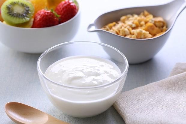 йогурт в прозрачной пиале, на фоне клубника, киви и орехи в тарелочках
