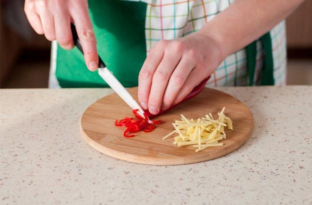 имбирь, нарезанный тонкой соломкой, и нарезанный красный перец на круглой разделочной доске на столе