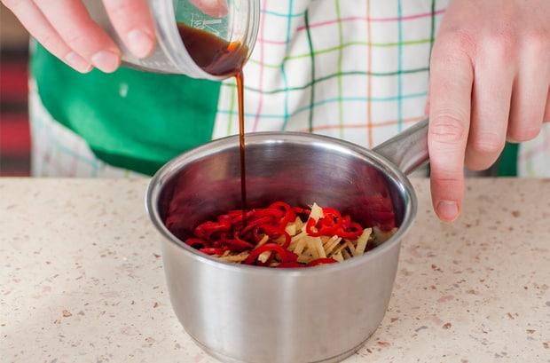 нарезанный имьирь с красным перцем в сотейнике на столе заливается соевым соусом