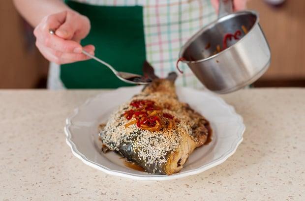 карп, запеченный целиком, посыпанный кунжутом и политый соусом из перца, на тарелке на столе