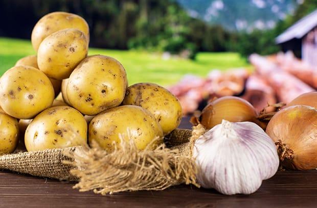 неочищенные картофель, лук и чеснок