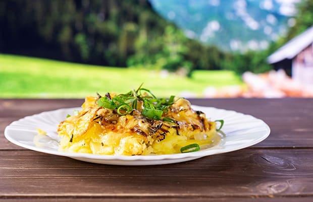 картофель, запеченный с луком и зеленью, на тарелке