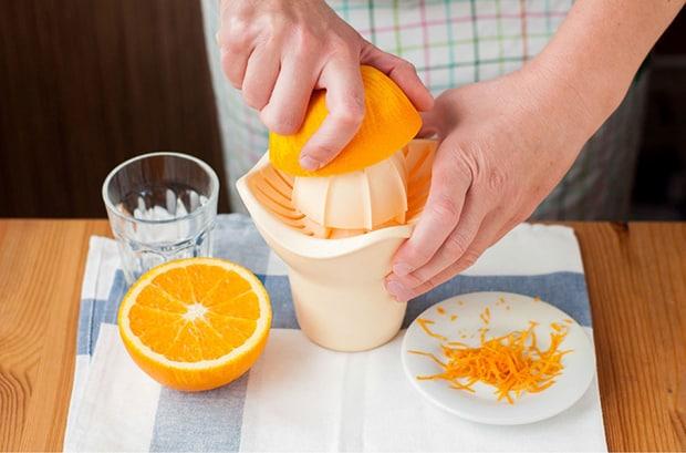 половинка апельсина выдавливается через соковыжималку, цедра на блюдце, стакан с водой и половинкой апельсина на столе, застеленном скатертью