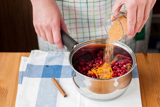тростниковый сахар пересыпается из стакана в сотейник с клюквой, рядом палочка корицы на столе, застеленном скатертью