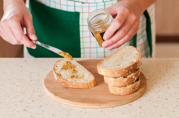 ломтики хлеба мажут горчицей