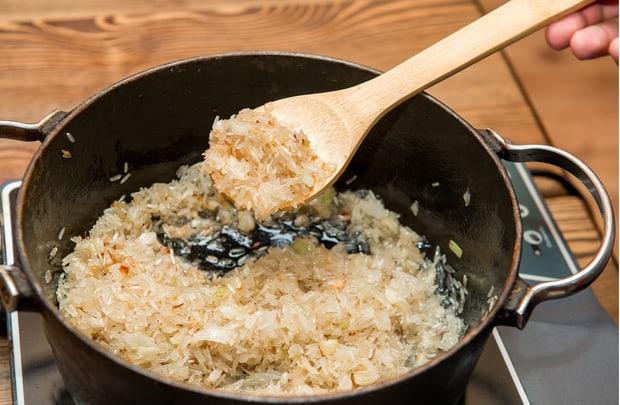 лук и рис в сковороде на плите
