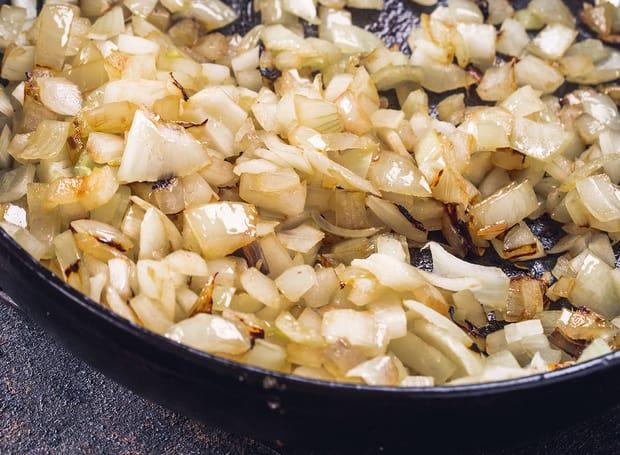 жареный нарезанный лук на сковороде