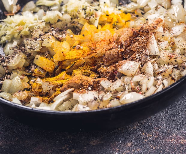 жареный нарезанный лук со специями в сковороде