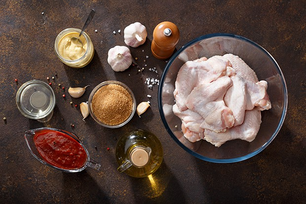 куриные крылышки, специи, чеснок. соус, масло на столе