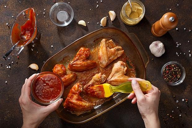 куриные крылышки смазывают соусом