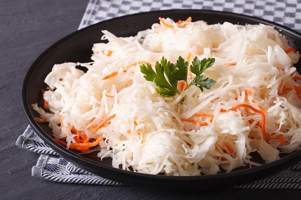 квашеная капуста с морковкой и веточкой петрушки в черной тарелке на столе, застеленном кухонным полотенцем
