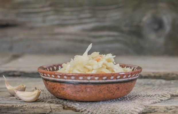 квашеная капуста в глиняной тарелке, рядом два зубчика чеснока