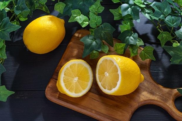 половинки лимона на разделочной доске, рядом целый лимон на столе с зеленой листвой