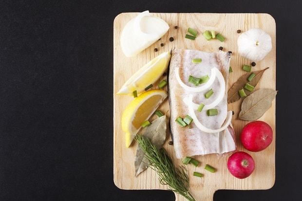 половина тушки минтая, редиска, дольки лимонов, укроп, лук и чеснок на разделочной доске