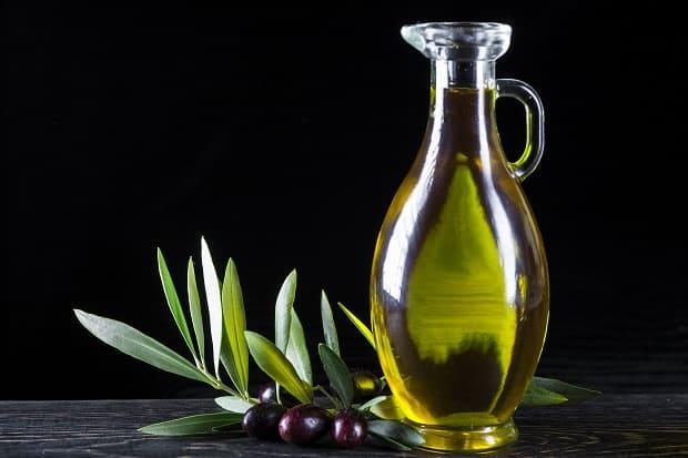 оливковое масло в графине, рядом маслины на ветке с листвой