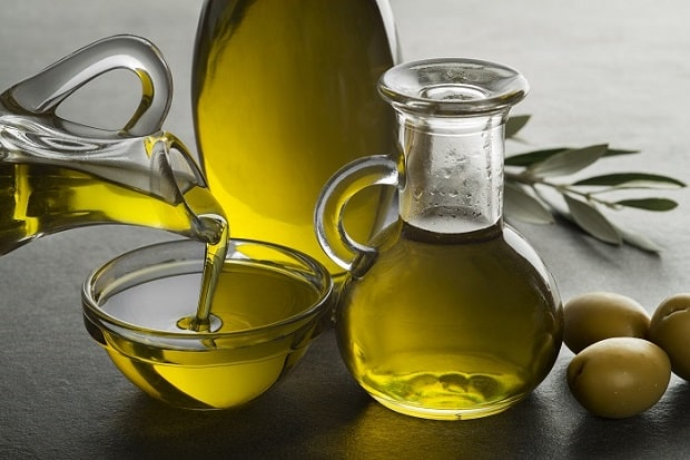 оливковое масло в графина и пиале, три свежие оливки