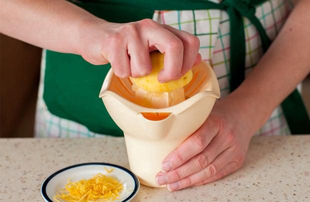 очищенный лимон в соковыжымалке, цедра на блюдце на столе