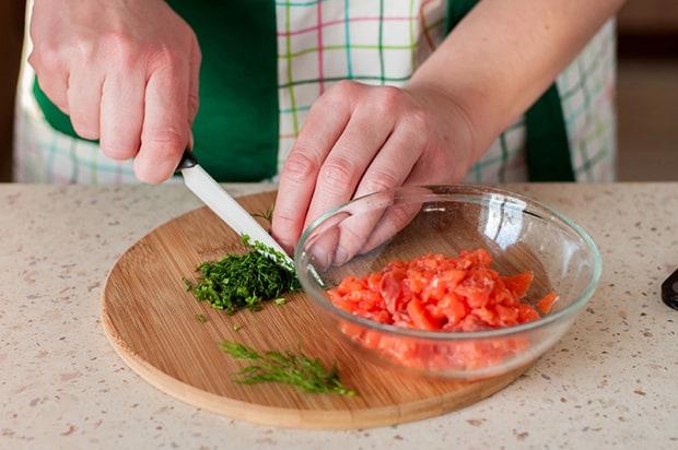 нарезанный лосось в прозрачной тарелке на круглой разделочной доске, рядом измельченная зелень