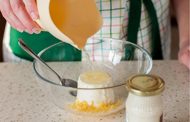 лимонный сок вливается тарелку со сливочным сыром, цедрой и ложкой