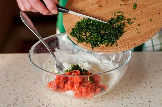 измельченная зелень добавляется в прозрачную тарелке с нарезнным лососем и сливочным сыром