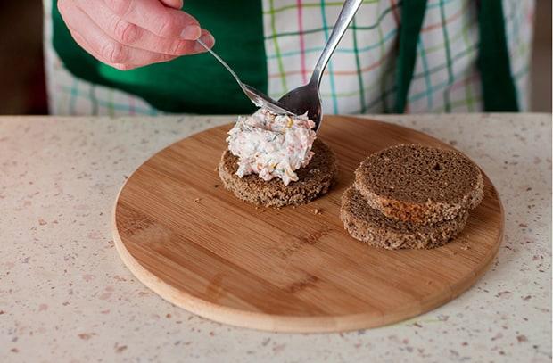 паштет из лосося выкладывается на кружочки черного хлеба на разделочной доске