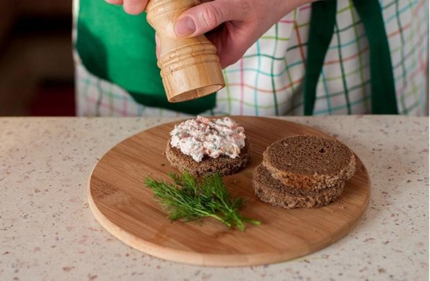 паштет из лосося на кружочке черного хлеба посыпается перцем,, рядом свежий укроп на круглой доске