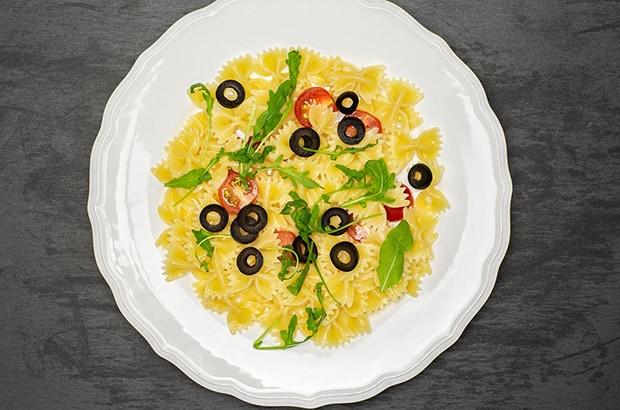 паста с овощами, рукколой и маслинами на тарелке