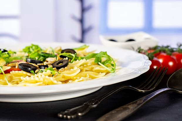 паста с овощами по-итальянски на белой тарелке