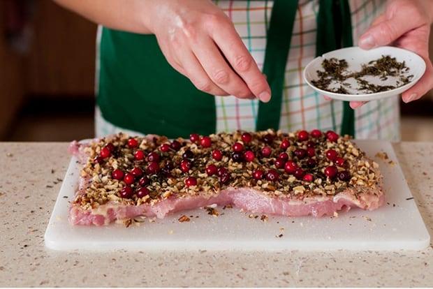 отбитый кусок свинины, посыпанный специями, на разделочной доске на столе