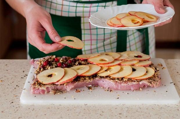 яблоки, нарезанные кольцами, выкладываются поверх отбитого куска свинины со специями на разделочной доске