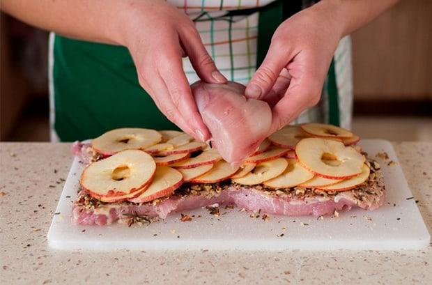 свежее куриное филе выкладывается поверх отбитого куска свинины со специями и яблоками на разделочной доске